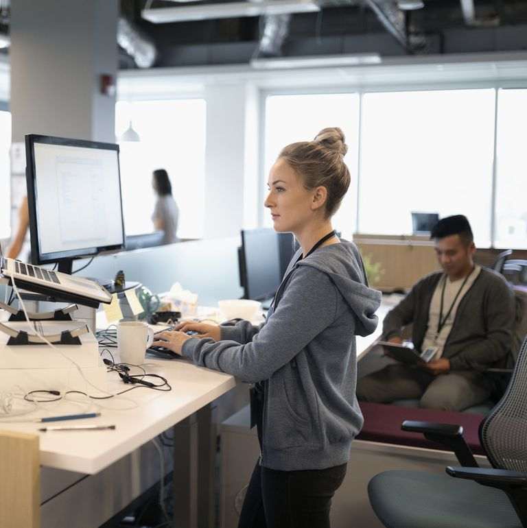 creative-businesswoman-standing-at-desk-using-royalty-free-image-1015140326-1558555972