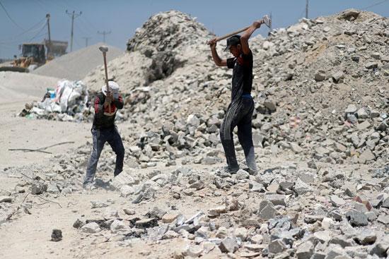 عمال-فلسطينيون-يكسرون-الحجر-لإعادة-استخدامه-فى-البناء