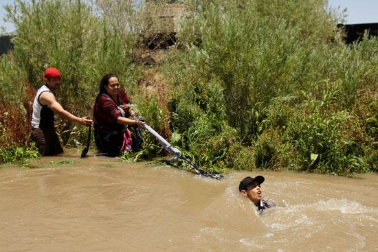 مهاجرون غير شرعيون يسحبون زميلهم من النهر