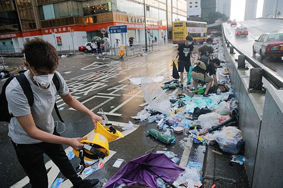 اشخاص يزيلون مخلفات اعتصامهم فى هونج كونج