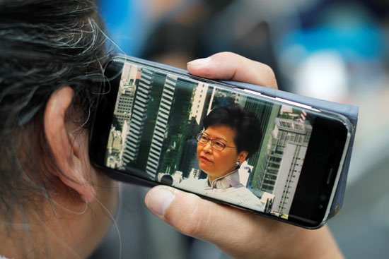 مواطن يستمع لخطاب كاري لام الرئيسة التنفيذية لهونج كونج عبر الهاتف
