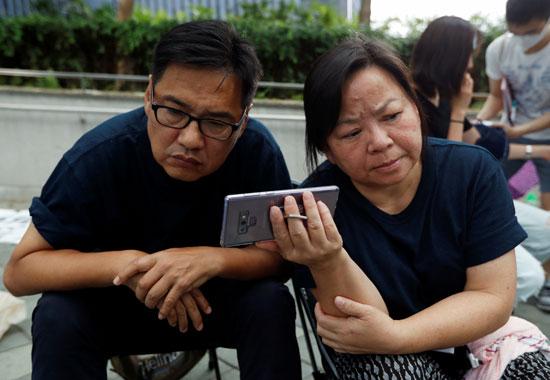 رجل وزوجته يتابعان خطاب كاري لام الرئيسة التنفيذية لهونج كونج عبر الهاتف