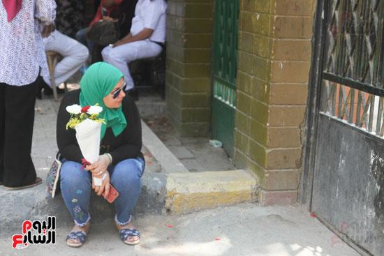 ام تنتظر ابنتها خارج المدرسة بالورود