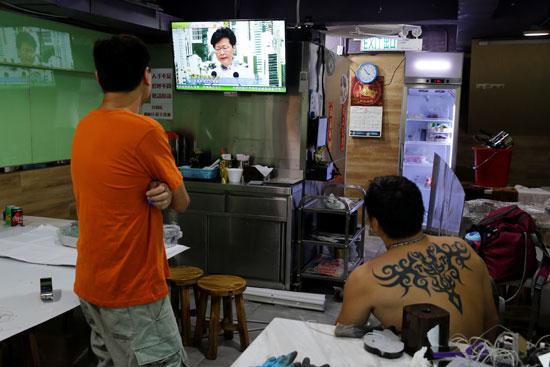 رجلان يتابعان خطاب كاري لام الرئيسة التنفيذية لهونج كونج