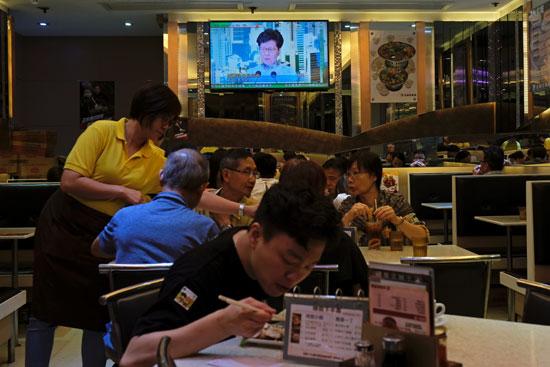 مواطنون يتابعون خطاب كاري لام الرئيسة التنفيذية لهونج كونج