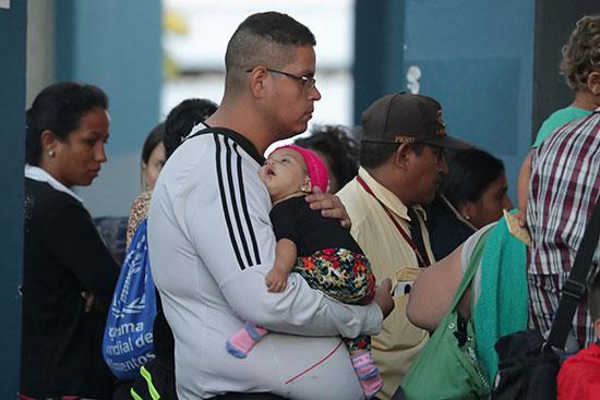 مهاجر يحمل ابنته