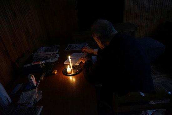 مواطن يباشر عمله على ضوء الشموع