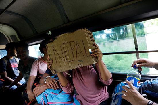 مهاجرة تحمل لافتة مكتوب عليها اسم دولتها نيبال