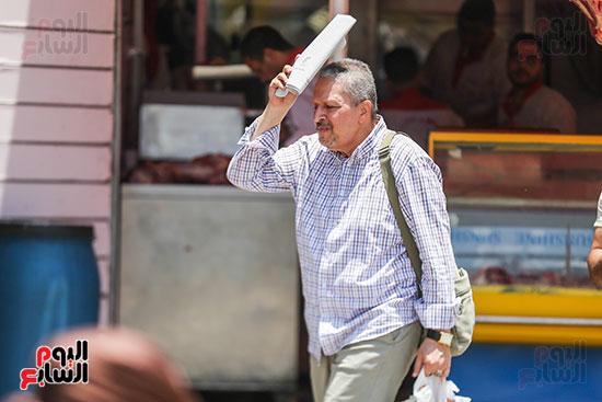 رجل-يحمل-الورق--تجنب-الحر