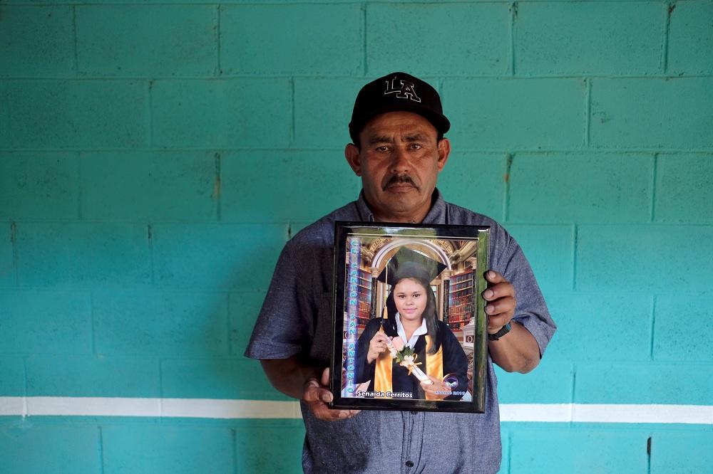 والد  ماريا سينايدا إسكوبار يحمل صورتها