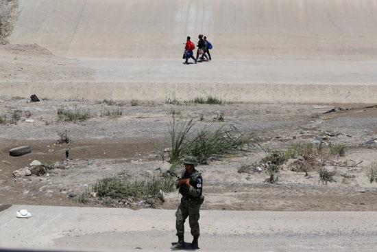 أسرة مهاجرة تتسلل خلف جندى مكسيكى