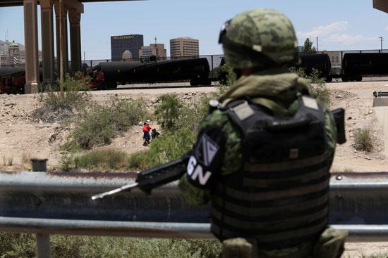 مهاجرين يتسللون بين الأشجار لعبور الحدود الأمريكية