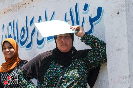 سيدة-تضع-الورق-فوق-رأسها-لتجنب-الشمس