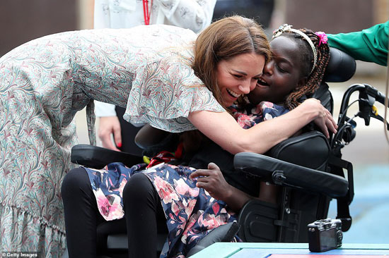 كيت تحتضن طفلة فى الجمعية الملكية للتصوير الفوتوغرافى
