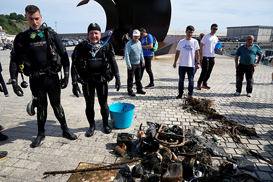 Divers and volunteers near shows the recovered waste material