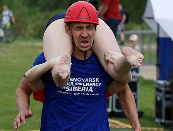 رجل يحمل زوجته خلال المسابقة