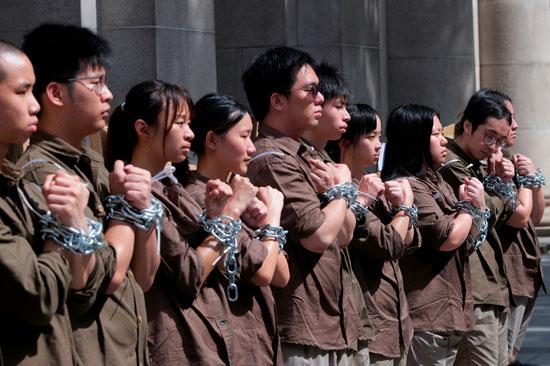 متظاهرون يقيدون أيديهم احتجاجا على القانون