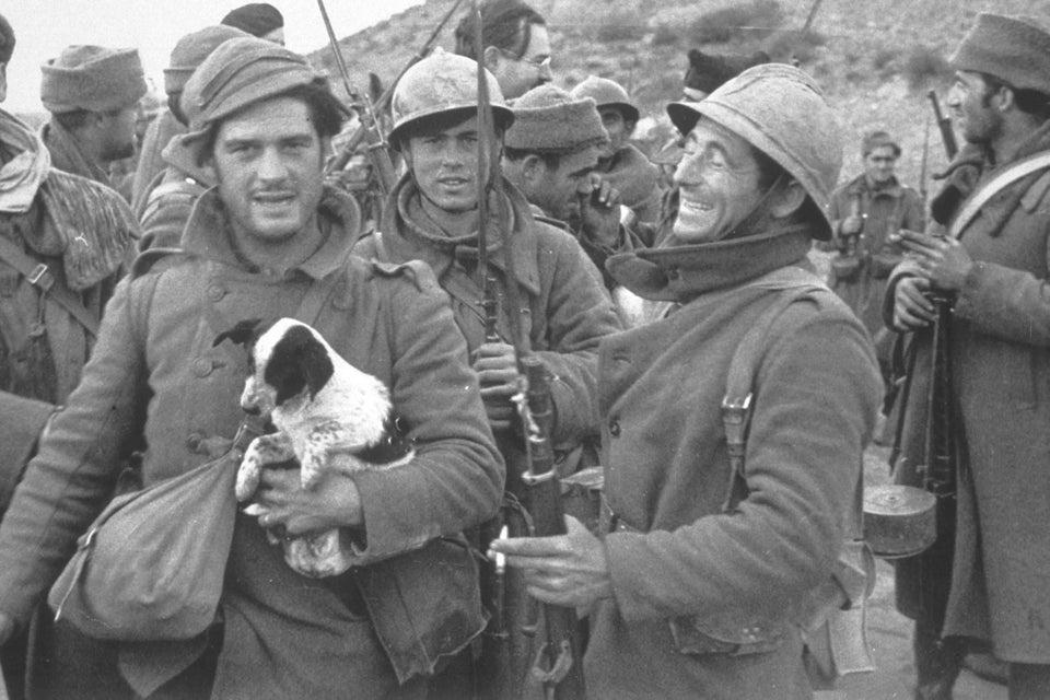 الروائي البريطاني جورج أورويل يحمل جرو أثناء توثيق الحرب الأهلية الإسبانية في عام 1937