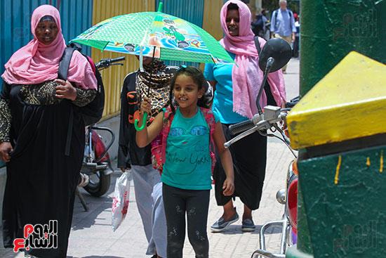 طفلة تحمل شمسية للوقاية من الحرارة في الجو