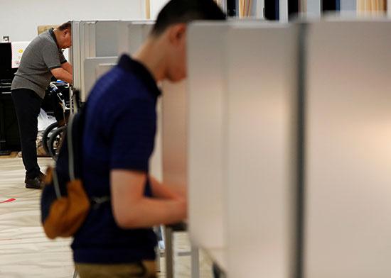 يدلى الناخبون بأصواتهم في محطة اقتراع أثناء انتخابات مجلس الشيوخ الياباني في طوكيو