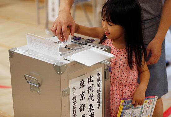 فتاة تساعد في الإدلاء بأصواتها في محطة اقتراع أثناء انتخابات مجلس الشيوخ الياباني في طوكيو