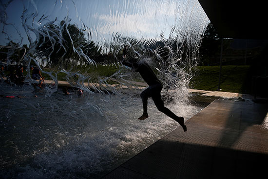 A young man moves into the water to escape the heat wave