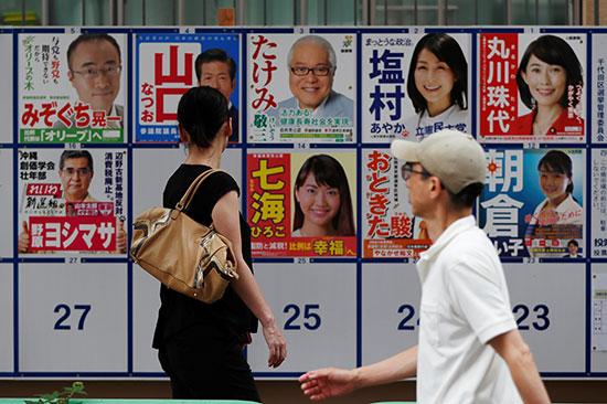 يمشي الناخبون عبر ملصقات الحملة الانتخابية خارج محطة الاقتراع أثناء انتخابات مجلس الشيوخ الياباني في طوكيو