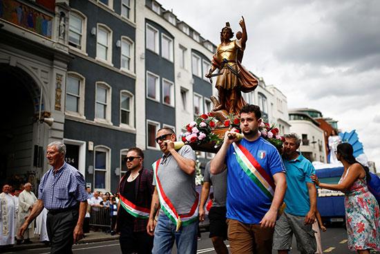 شباب يحملون تمثال القديسة