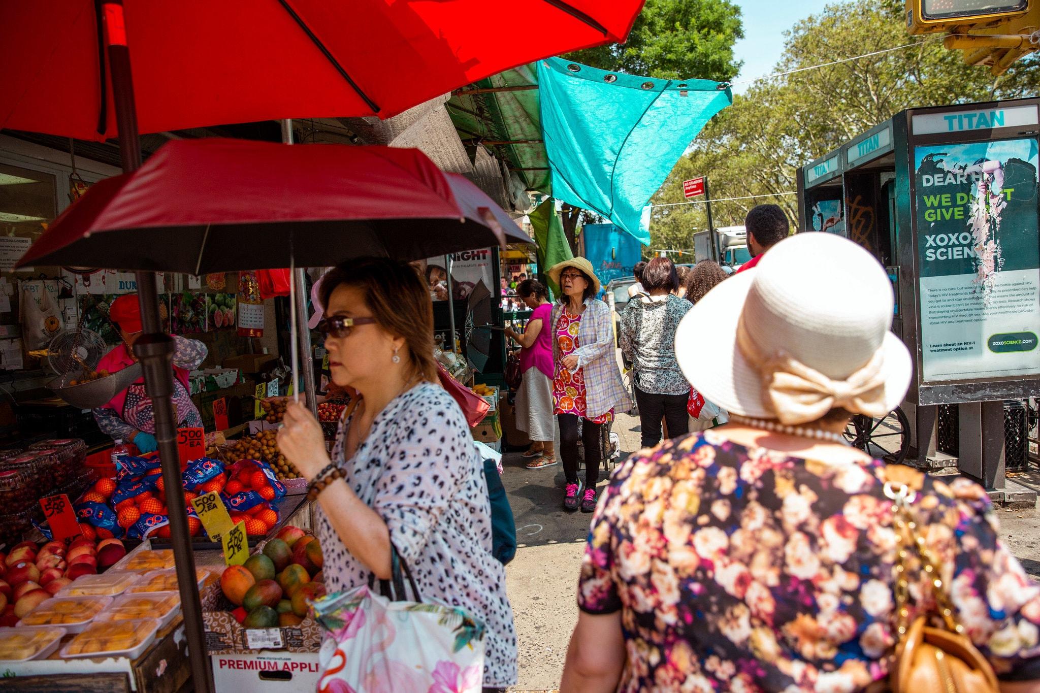 زوار الحى الصينى فى نيويورك يستخدمون الشماسى للوقاية من الشمس