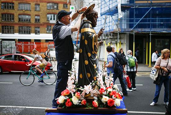 أحد المشاركين يجهز تمثالا قبل الموكب