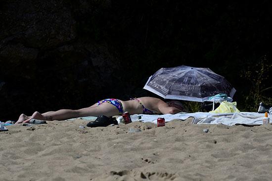 أوروبية تفترش الرمال بأحد الشواطئ