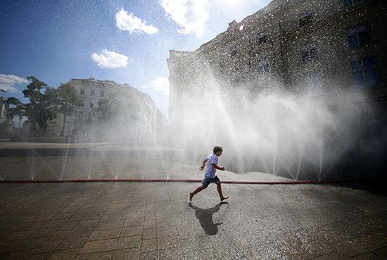مواطن يسير بجوار النافورات هربا من حرارة الجو