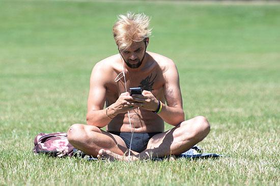 رجل يجلس بأحد الحدائق بدون ملابسه بسبب الطقس الحار