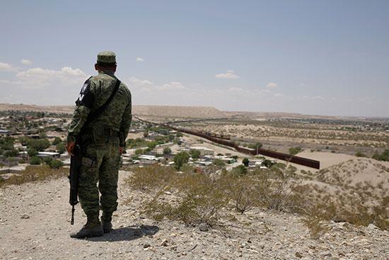 حارس امن مكسيكى ينظر للسياج الحدودى مع امريكا