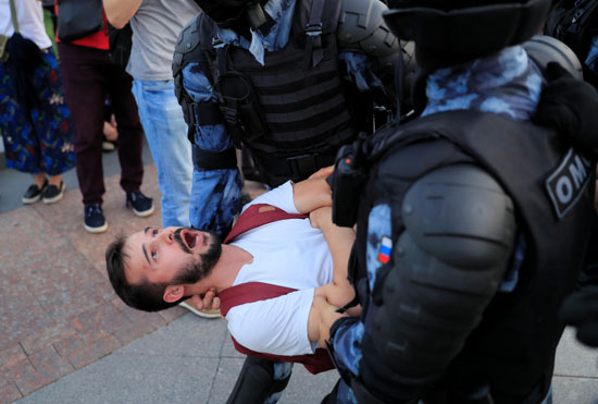 Police holding a demonstrator during protests