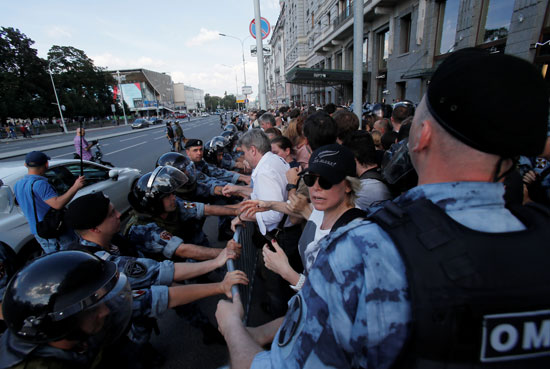 Russian anti riots police pushes the demonstrators away from the street