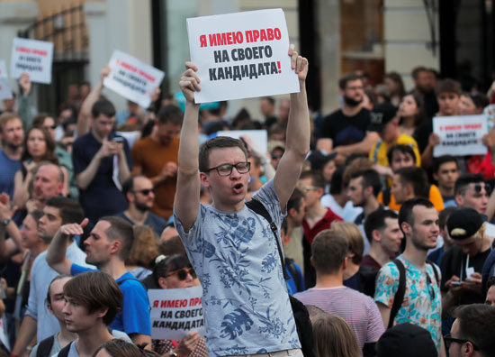 Young man holding a playcard during Moscow protests