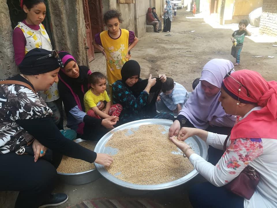 عضوان القومى للمرأة ينظفون القمح بحملة طرق الأبواب (1)