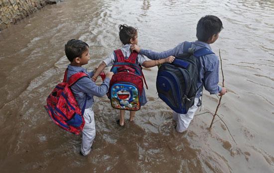 تلاميذ يسيرون وسط المياه