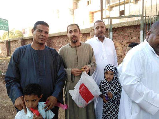 شاب قبطي يوزع الحلوي والبالونات علي أطفال قرية الشغب جنوبي الأقصر إحتفالاً بعيد الأضحي (4)