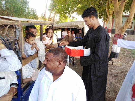 شاب قبطي يوزع الحلوي والبالونات علي أطفال قرية الشغب جنوبي الأقصر إحتفالاً بعيد الأضحي (5)