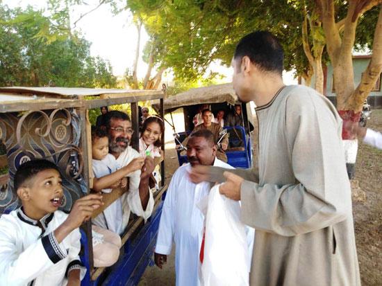شاب قبطي يوزع الحلوي والبالونات علي أطفال قرية الشغب جنوبي الأقصر إحتفالاً بعيد الأضحي (1)