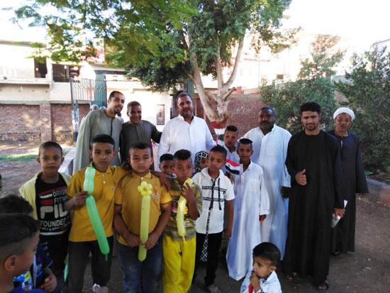 شاب قبطي يوزع الحلوي والبالونات علي أطفال قرية الشغب جنوبي الأقصر إحتفالاً بعيد الأضحي (8)