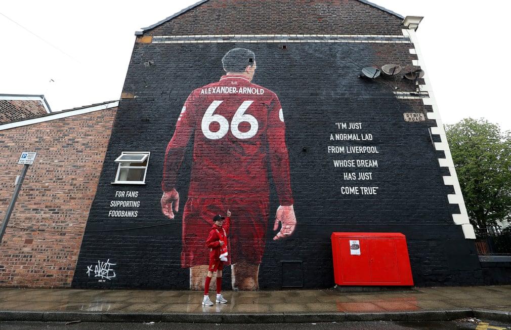 أحد المعجبين يلتقط صورة بجانب لوحة جدارية رائعة لأرنولد على جدار أنفيلد
