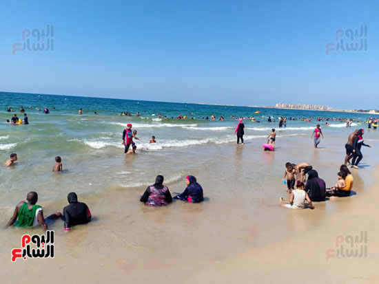 السيدات يلعبون مع اولادهم فى البحر