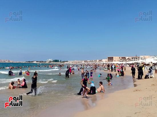 الاطفال على الشاطئ مع اسرهم