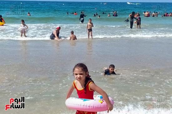 طفلة تلعب بالعوامة على الشاطئ