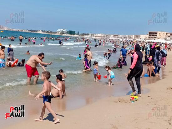 الاسر يلعبون مع اطفالهم فى البحر
