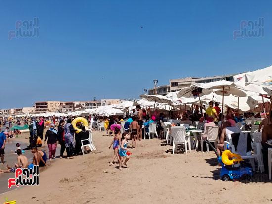 الاطفال والكبار يستمتعون بالبحر والرمال
