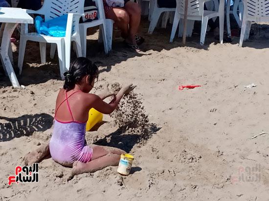 احدى الاطفال تبنى الاهرامات وبيوت من الرمال